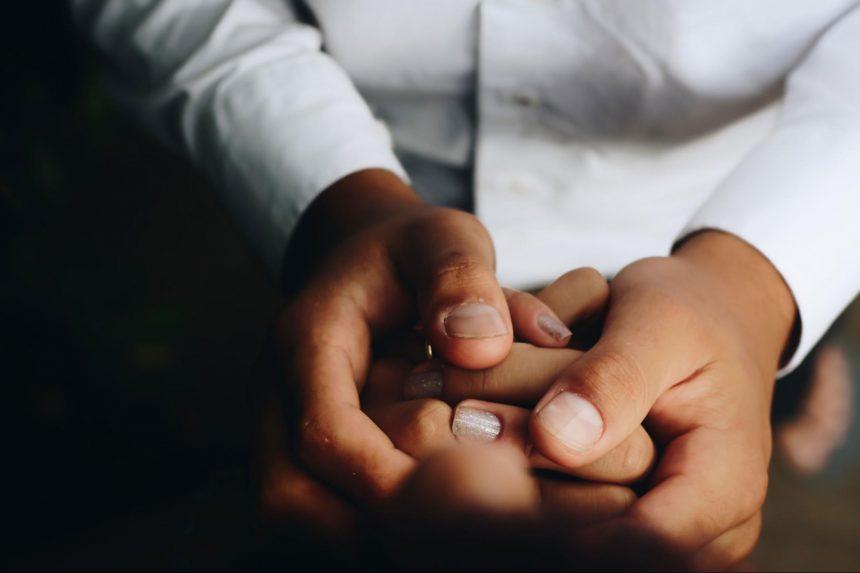 患者の手を握る医者
